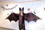 Bat costume, wings outstretched.